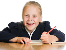 Schoolgirl writes at a table Royalty Free Stock Image
