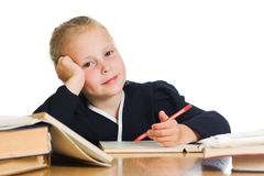 Schoolgirl writes at a table Stock Photography