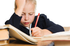 Schoolgirl writes at a table Royalty Free Stock Photos