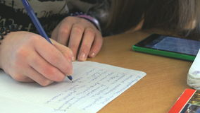Schoolgirl writes the text on white sheet of paper stock video