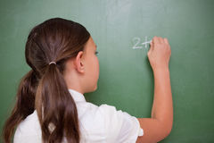 Schoolgirl writing an addition Royalty Free Stock Photo