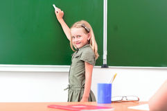 Schoolgirl writing on a blackboard Royalty Free Stock Images