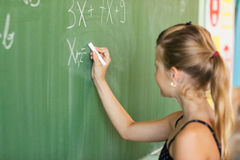 Schoolgirl Writing on the Blackboard Royalty Free Stock Image