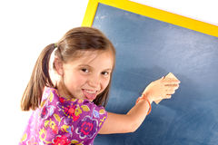 Schoolgirl writing on a blackboard Royalty Free Stock Photos