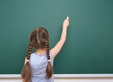 Schoolgirl writing chalk on a blackboard, empty space, education concept Stock Images