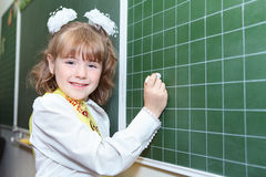 Schoolgirl writing by chalk on green blackboard Stock Image