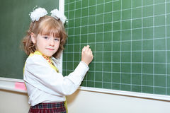 Schoolgirl writing by chalk on green blackboard Stock Images