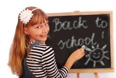 Schoolgirl writing on chalkboard Stock Images