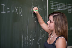 Schoolgirl writing on the chalkboard Royalty Free Stock Images