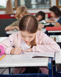 Schoolgirl Writing At Desk Royalty Free Stock Photography