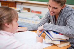 Schoolgirl writing with her smiling teacher Royalty Free Stock Images