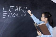 Schoolgirl writing learn english word on board Royalty Free Stock Photo