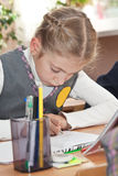 Schoolgirl writing in a notebook Stock Photography