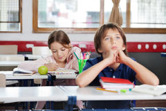 Schoolgirl Writing Notes In Classroom. Little school girl writing notes with thoughtful boy in foreground at classroom Royalty Free Stock Images