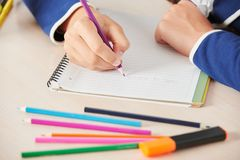 Schoolgirl writing while sitting in school desk Royalty Free Stock Images