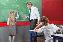 Schoolgirl Writing With Teacher Standing By Board Stock Photo