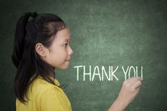 Schoolgirl writing thank you text on a chalkboard