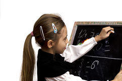 Schoolgirl wrote on the blackboard. On a white background Royalty Free Stock Image