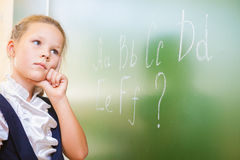 Schoolgirl wrote in chalk on blackboard and teach English language Royalty Free Stock Photo