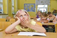 Schoolgirl yawning Stock Images