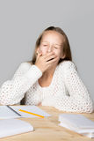 Schoolgirl yawning beside textbooks Royalty Free Stock Photos