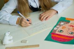Schoolgirlen skriver i tetrads arkivfoto