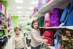 First graders choosing briefcase in store for school. Schoolgirls buying briefcase for school at store royalty free stock photography