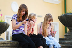 Schoolgirls calling on the phones Stock Photography