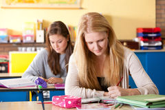 Schoolgirls in the classroom. Two attractive teenagers in the classroom studying together Royalty Free Stock Photography
