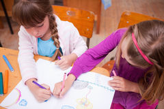 Schoolgirls drawing in a coloring book Royalty Free Stock Images