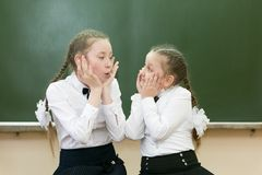 Teen girls laugh on the background of the school board. Schoolgirls girlfriends having fun in classroom of the school at recess make funny faces on their faces royalty free stock photography