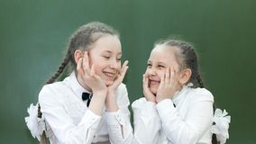 Teen girls laugh on the background of the school board. Schoolgirls girlfriends having fun in classroom of  school at recess make funny faces on their faces stock photos