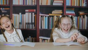 Schoolgirls having fun together on school lesson in class room. Funny teenager girl showing funny tricks with hair. Braids. Joyful classmates laughing on stock footage