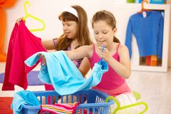 Schoolgirls helping with housework. Putting clothes away, smiling royalty free stock images