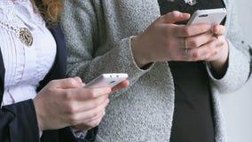 Schoolgirls hold smart phones in hands indoors stock video footage