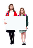 Schoolgirls holding big blank banner ad Royalty Free Stock Image