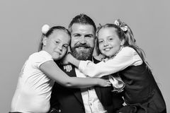 Schoolgirls hug their dad father isolated on yellow background. Kids wearing school clothes sit next to bearded father. Girls and men with happy faces. Back to stock image