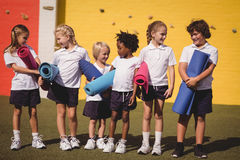 Schoolgirls interacting with each other while holding exercise mat. In schoolyard Stock Photo