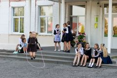 Schoolgirls jump on a rope at a change in front of the school Royalty Free Stock Photography