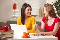 Schoolgirls laughing at table Stock Image