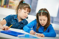 Schoolgirls learning in classroom stock photography