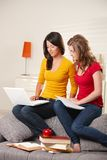 Schoolgirls learning on couch at home Royalty Free Stock Photos
