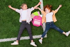 Schoolgirls lying on grass Stock Images