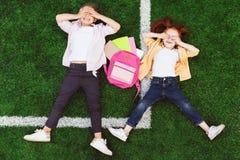 Schoolgirls lying on grass Stock Photos