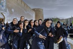 Schoolgirls near medieval fortress Arg of Karim Khan, Shiraz, Ir. Fars Province, Shiraz, Iran - 19 april, 2017: A group of Iranian schoolgirls having fun and stock photography