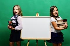 Schoolgirls next to whiteboard on green background stock photos