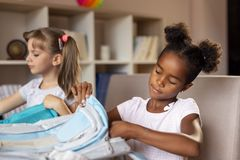 Schoolgirls packing bags for school royalty free stock photography