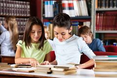 Schoolgirls Reading Book Together At Table In Royalty Free Stock Photo