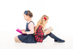 Schoolgirls reading books. Schoolgirls sitting and reading books on white Royalty Free Stock Image