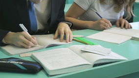 Schoolgirls and schoolboy sitting at a school desk. The schoolgirls and schoolboy sitting at the school desk deciding the home task in a notebook indoors stock footage